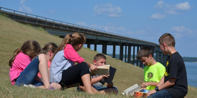 Children at the Trinity River bridge discussing a book they've read.